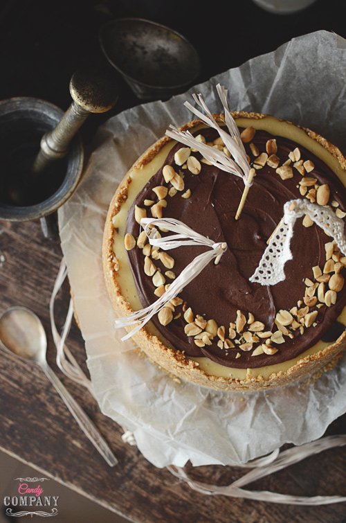 Creamy peanut butter zebra cheesecake on graham crust, with chocolate ganache and peanuts