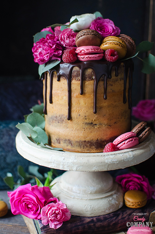 Flourless chocolate almond cake with caramelized white chocolate ganache and raspberries decorated with fresh flowers and french macaroons